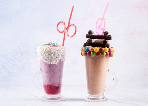 Vista frontal dos copos de sobremesa com canudos e doces coloridos