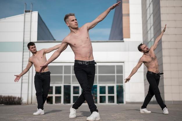 Vista frontal dos dançarinos de hip hop sem camisa ensaiando lá fora
