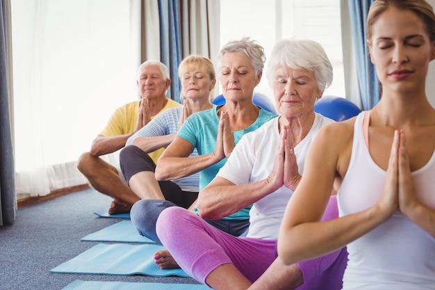 Vista frontal dos idosos relaxantes com instrutor de fitness