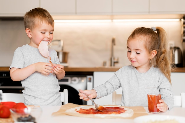 Vista frontal dos irmãos cozinhando em casa