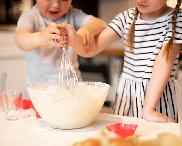 Vista frontal dos irmãos fofos cozinhando em casa