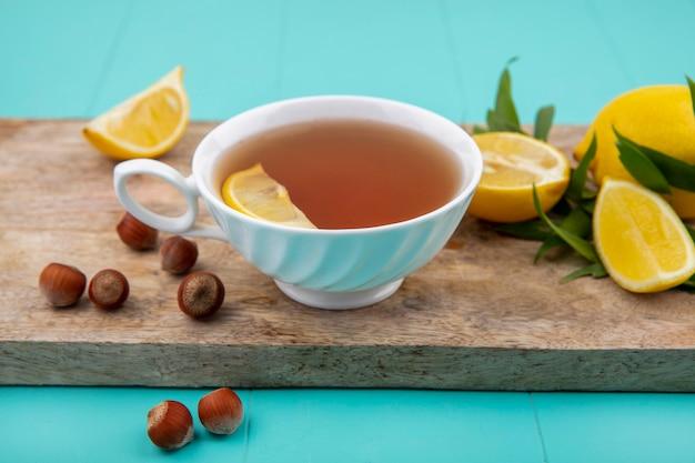 Vista frontal dos limões em uma placa de cozinha de madeira com uma xícara de avelãs de chá na superfície azul