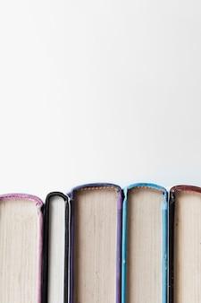 Vista frontal dos livros no fundo liso, com espaço de cópia