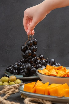 Vista frontal dos melhores petiscos deliciosos em uma velha corda de jornal e a mão segurando uma uva preta
