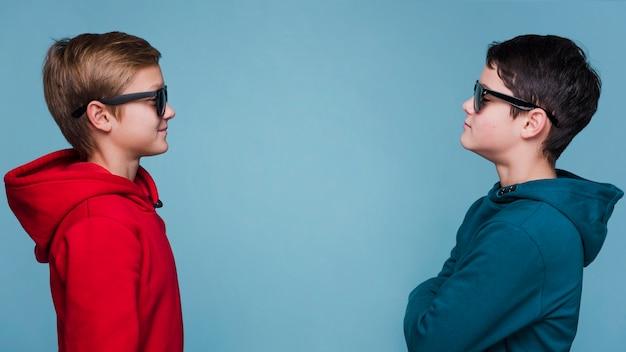Vista frontal dos meninos, olhando um ao outro com espaço de cópia