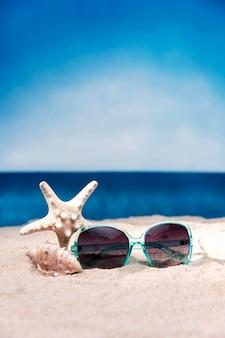 Vista frontal dos óculos de sol e estrela do mar na praia