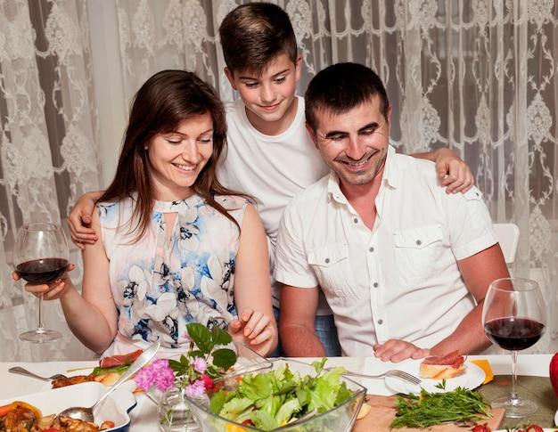 Vista frontal dos pais com o filho na mesa de jantar