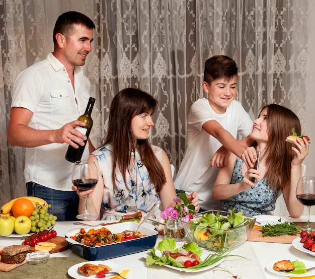 Vista frontal dos pais com os filhos na mesa de jantar