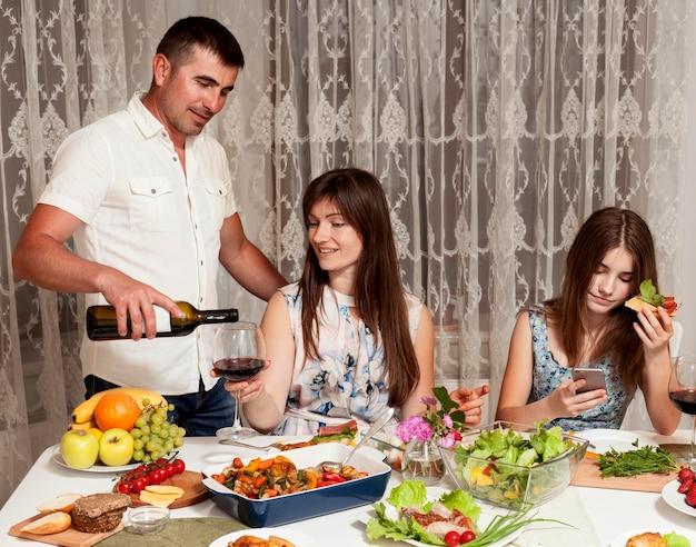 Vista frontal dos pais e filha na mesa de jantar