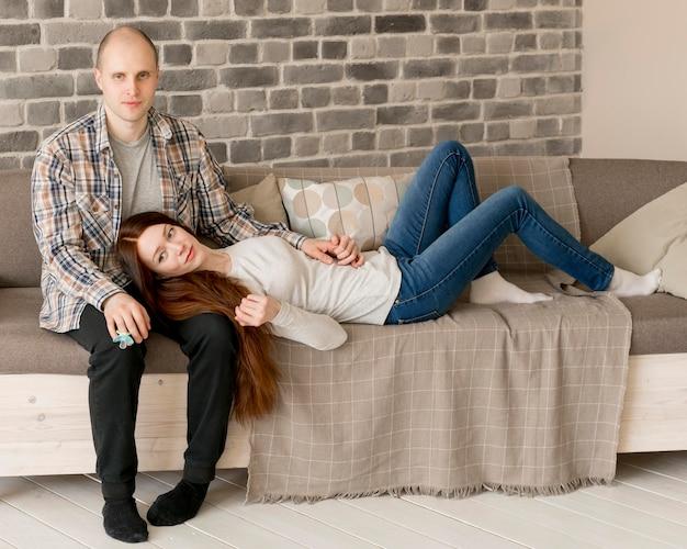 Vista frontal dos pais sentados no sofá