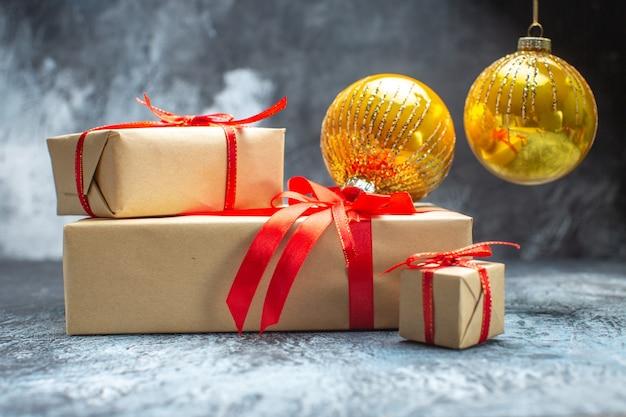 Vista frontal dos presentes de natal amarrados com laços vermelhos e brinquedos na foto claro-escuro foto do feriado de ano novo presente de natal