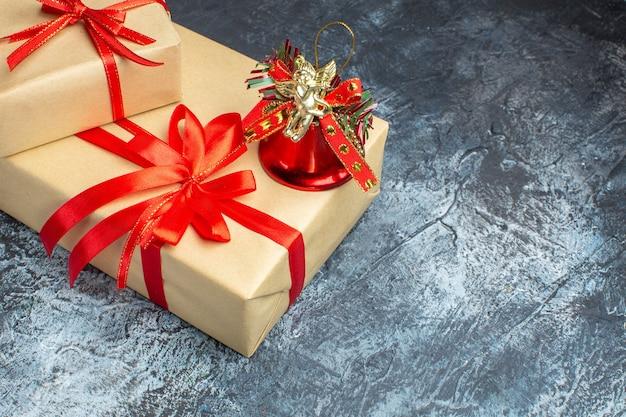 Vista frontal dos presentes de natal amarrados com laços vermelhos em foto de natal de ano novo de cor claro-escuro