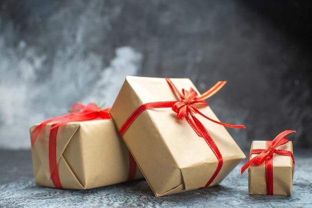 Vista frontal dos presentes de natal amarrados com laços vermelhos na foto colorida claro-escuro natal presente de natal