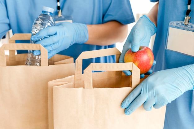 Vista frontal dos sacos de doação sendo preparados com alimentos