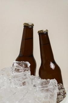 Vista frontal duas garrafas de cerveja em cubos de gelo frio