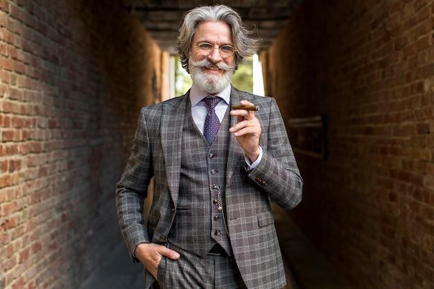 Vista frontal elegante homem maduro fumando Foto gratuita