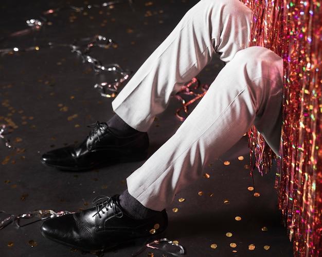 Vista frontal elegantes sapatos com calças e uma cortina de brilhos