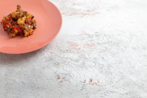 Vista frontal em fatias de carne cozida com molho dentro do prato na superfície branca