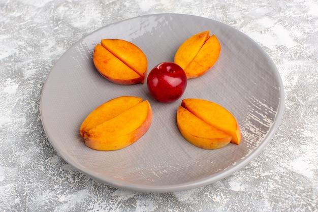 Vista frontal em fatias de pêssegos frescos dentro da placa alinhada na mesa branca clara.