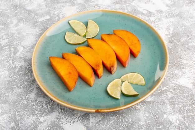 Vista frontal em fatias de pêssegos frescos dentro do prato com limões fatiados na mesa branca clara.