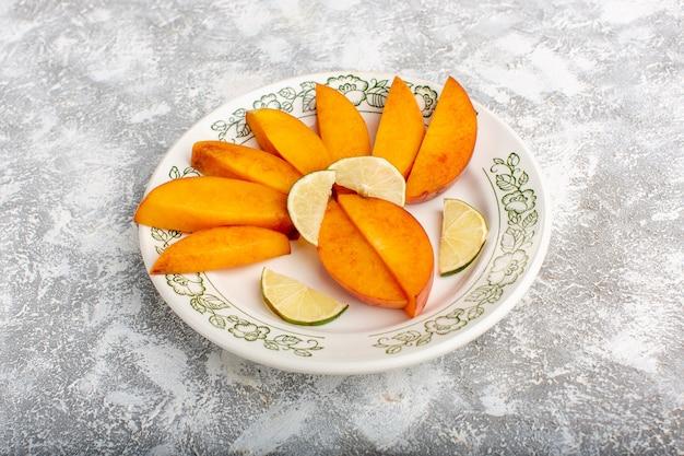 Vista frontal em fatias de pêssegos frescos dentro do prato com limões na mesa branca clara.