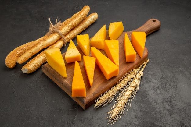 Vista frontal em fatias de queijo fresco com pãezinhos em uma foto escura de lanche crocante de café da manhã