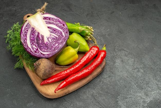 Vista frontal em fatias de repolho roxo com outros vegetais na mesa escura, salada saudável, dieta madura