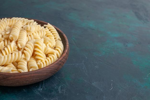 Vista frontal em forma de massa italiana deliciosa, parecendo pequena massa dentro de uma panela marrom na mesa azul escura