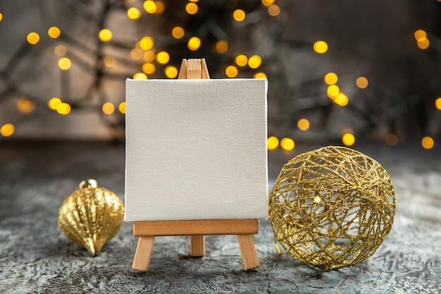 Vista frontal em tela branca em cavalete de madeira com luzes de natal com detalhes de natal em fundo escuro