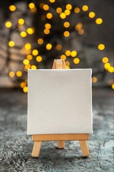 Vista frontal em tela branca em cavalete de madeira luzes de natal no escuro
