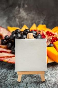 Vista frontal em tela branca em cavalete de madeira uvas pedaços de queijo fatias de carne em placa de madeira no escuro