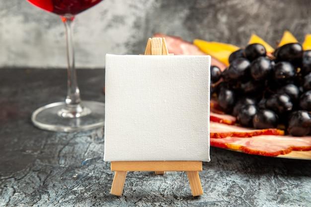 Vista frontal em tela branca no cavalete de madeira, uvas para vinho, fatias de carne na placa de madeira no escuro