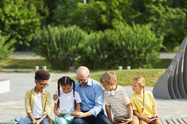 Vista frontal em um grupo multiétnico de crianças usando tablets e smartphones enquanto está sentado na fila ao ar livre sob a luz do sol com um homem maduro ajudando-os