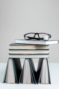 Vista frontal empilhados livros com fundo cinza