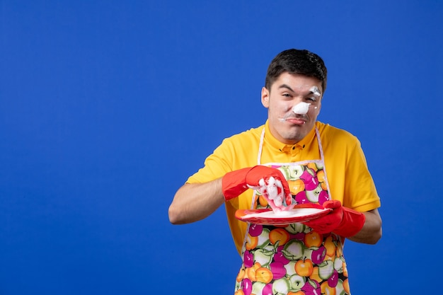 Vista frontal, empregada masculina engraçada com espuma no prato de lavagem de rosto no espaço azul