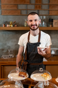 Vista frontal empregado masculino servindo café