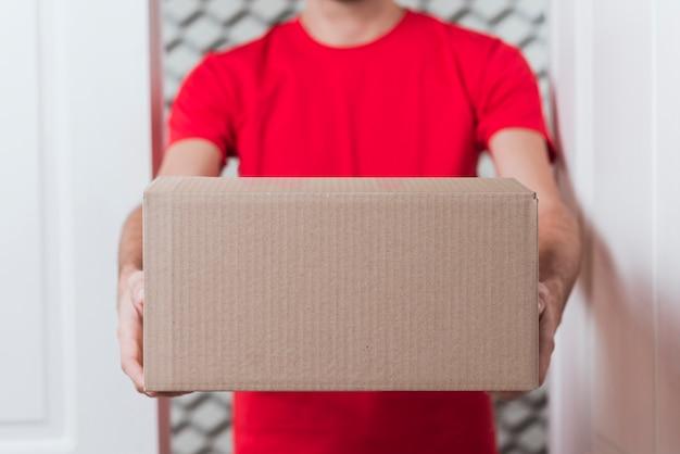 Vista frontal entrega homem vestindo uniforme vermelho close-up