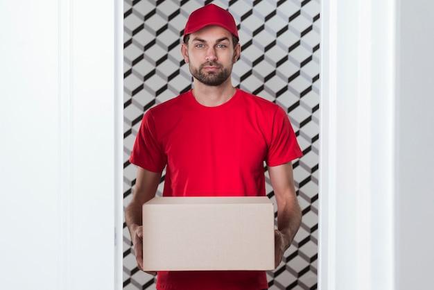 Vista frontal entrega homem vestindo uniforme vermelho