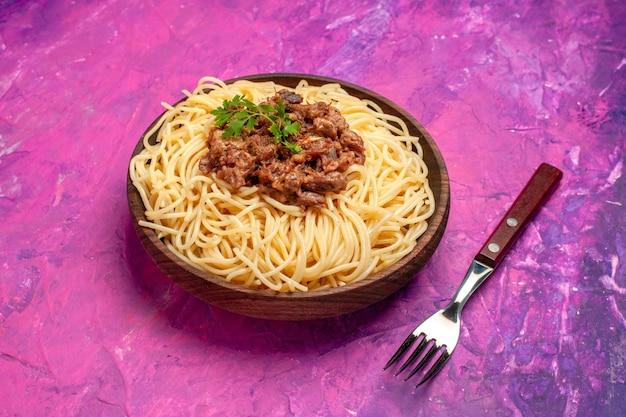 Vista frontal espaguete cozido com carne moída em macarrão de massa de prato de cor rosa