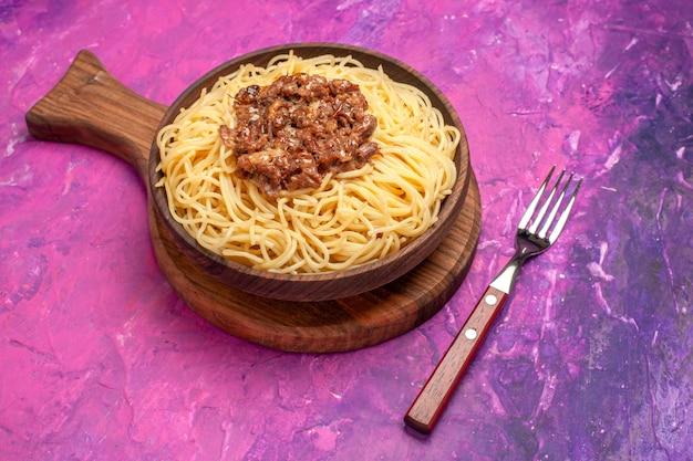 Vista frontal espaguete cozido com carne moída em prato de massa de mesa rosa temperos para massas