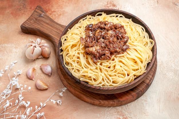 Vista frontal espaguete cozido com carne moída em temperos de prato de massa de massa de mesa de madeira