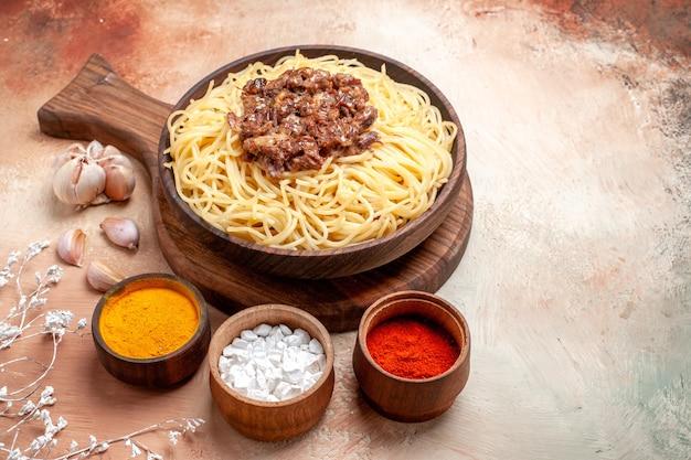 Vista frontal espaguete cozido com carne moída na mesa de madeira, tempero para prato de massa