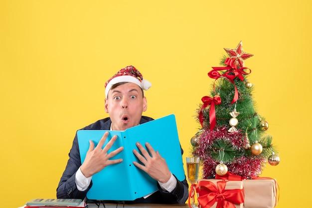 Vista frontal espantada com o homem de negócios sentado à mesa perto da árvore de natal e presentes sobre fundo amarelo