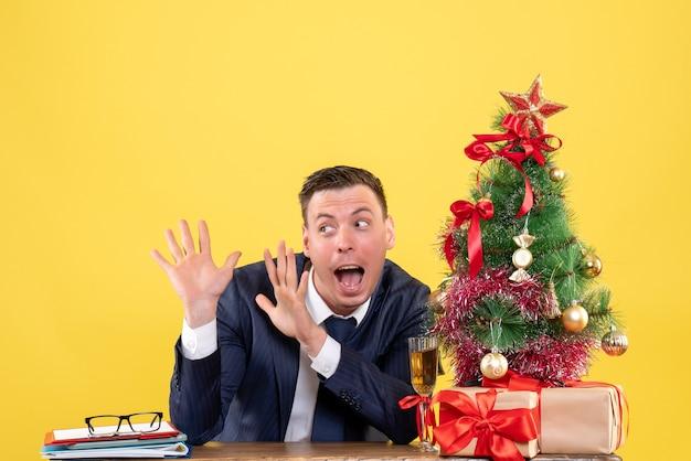 Vista frontal espantada com o homem de terno abrindo as mãos, sentado à mesa perto da árvore de natal e presentes em fundo amarelo