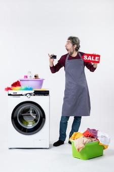 Vista frontal espantada com o homem segurando um cartão e uma placa de venda em pé perto da máquina de lavar no fundo branco
