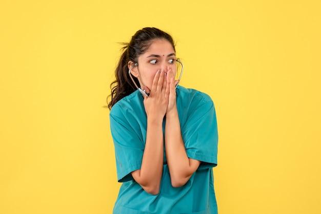 Vista frontal espantada, mulher médica de uniforme, colocando as duas mãos no rosto em fundo amarelo