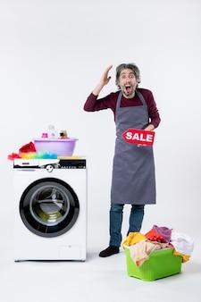 Vista frontal espantado jovem com avental segurando uma placa de venda em pé perto da máquina de lavar no fundo branco