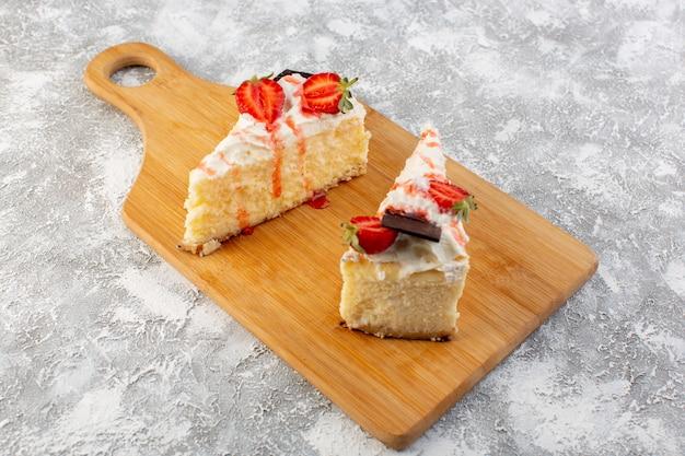 Vista frontal estreita fatias de bolo delicioso com creme de chocolate e morango