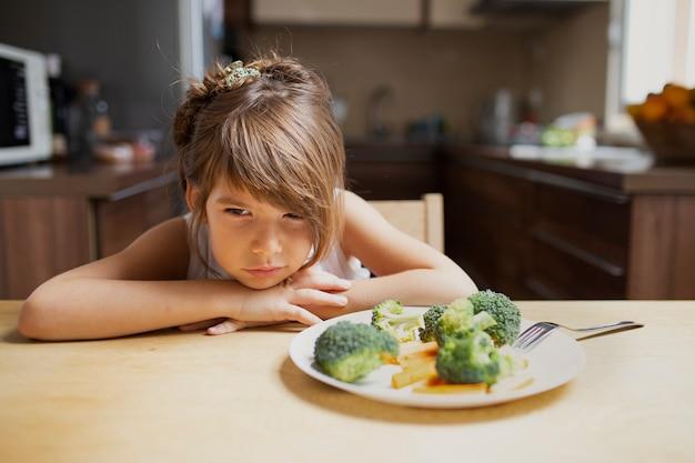 Vista frontal exigente menina recusar legumes