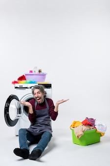 Vista frontal exultante governanta sentada em frente à máquina de lavar, abrindo o cesto de roupa suja com as mãos no fundo branco